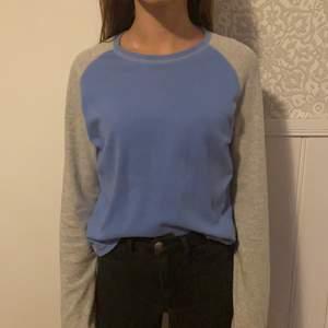 Grå och blå tröja, det står att det är storlek L men väldigt liten i storleken. Passar bättre på S (modellen på bilden har storlek S). Köparen står för frakten.