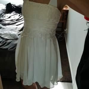 Vit finklänning. Med spets mönster vit bysten. Knytband i ryggen. Jättefin och en utav mina favoriter!