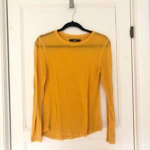 Gul långärmad ganska tunn tröja i T-shirt tyg. Mycket fint skick, använd ca 10 ggr.