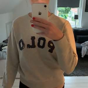 Grå Polo Ralph Lauren sweatshirt med marinblått tryck. Den är supeeeeeeer mjuk och bara använd några få gånger. Strl S men passar folk mellan 160-175cm. Köpt i New York. Hör gärna av dig vid intresse, pris kan diskuteras!