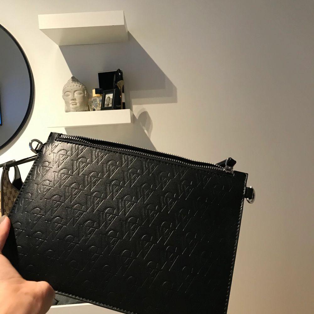 Oanvänd Carin Wester väska, svart men monogram, skit snygg och perfekt för utgång eller till skolan,helt ny. Accessoarer.