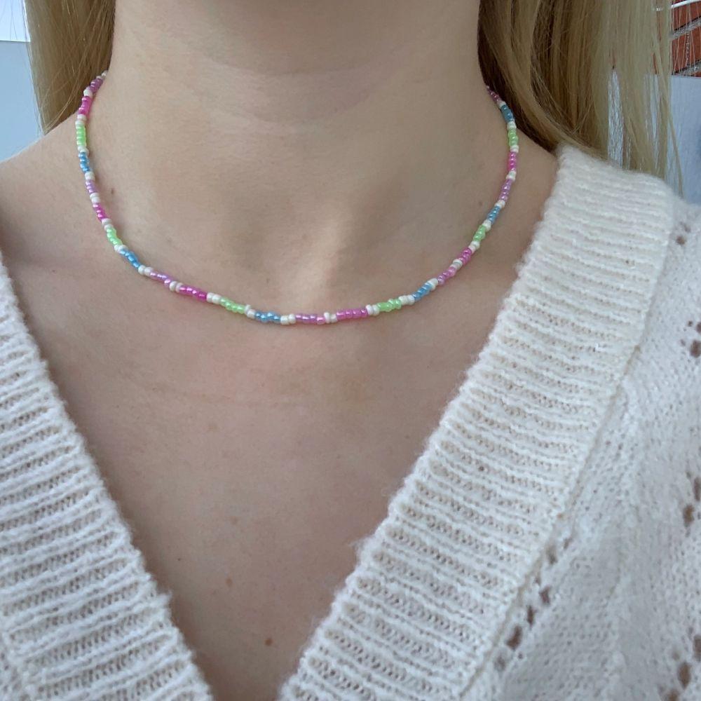 Flerfärgat pärlhalsband med små pärlor💚💜💞💙🤍🦋🍬🤩🥺 halsbandet försluts med lås och tråden är elastisk . Accessoarer.