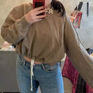 Croppad hoodie från bikbok som går o regleras där nere! Skulle säga att den är olivgrön