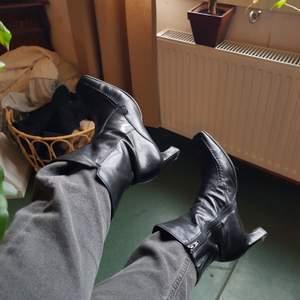 Supersnygga och bekväma fodrade klackar från 90-talet. I fint skick med mjukt äkta läder. På insidan har skorna pu-läder som lining mot dragkedjan, detta har börjat spricka upp p.g.a. ålder, men stör ingen funktion och syns ej. I storlek 39, passar också bra på en 39/40. Först till kvarn, samfraktar!