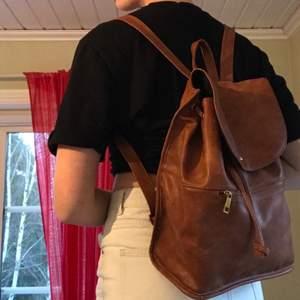 Fin, brun och rymlig ryggsäck i läderimmitation från ASOS. Helt oanvänd så i väldigt bra skick. Justerbara band och ett snöre som man kan dra åt för att stänga väskan. Ytterfack och innerfack som stängs med dragkedja. Frakt: 40kr