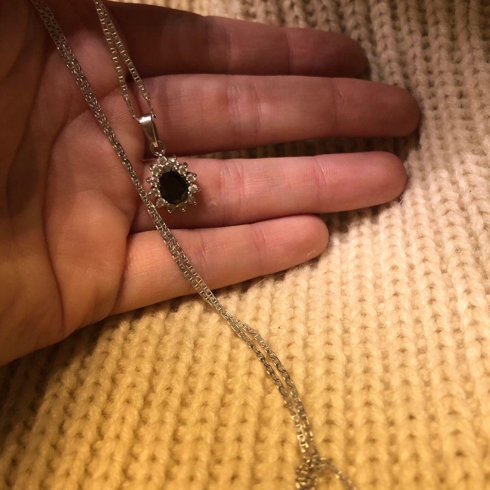 Halsband i silver med ett hängsmyckr med blå detalj.. Accessoarer.