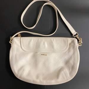 En vit läder väska från Furla som jag har använt väldigt mycket men den har kvar att ge. En cross body messenger väska med rem och gyllene detaljer