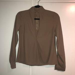 Urringning i mitten av tröjan. Brösten syns ej, mer som en detalj. Tröjan är lite ljusare i verkligheten. Använt någon gång.