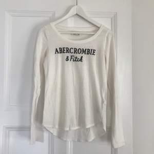 Vit tröja med  text från Abercrombie & Fitch.