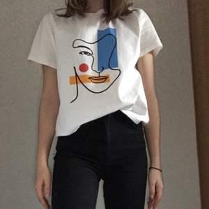 Vit t-shirt med tryck från SHEIN.  Säljer för jag har två likadana. Det finns en liten fläck på axeln, men den syns knappt (blir tydligare när man tar kort med blixt som jag har gjort). - Använd typ en gång - Storlek XS - 90 kr + frakt 40 kr
