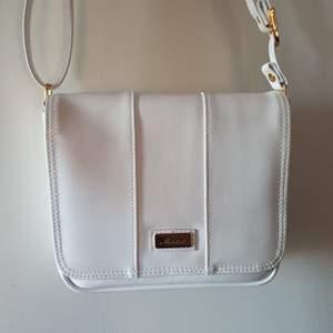 En vit snygg väska som med band som kan kortas och förlängas utifrån vad som önskas. Flera fack, varav två med dragkedja 🥰❤️ pris kan diskuteras