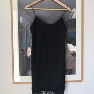 Snygg svart klänning med spetsdetaljer! Har nopprat sig lite (kan ses på tredje bilden), då jag råkade gå in i ett staket :-)  Möts ej upp, skickar endast, men frakten ingår i priset!