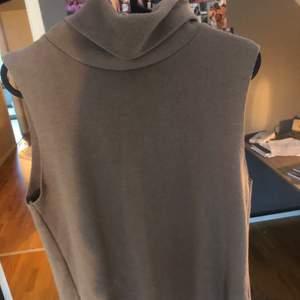 Ett beiget linne med polokrage i storlek M