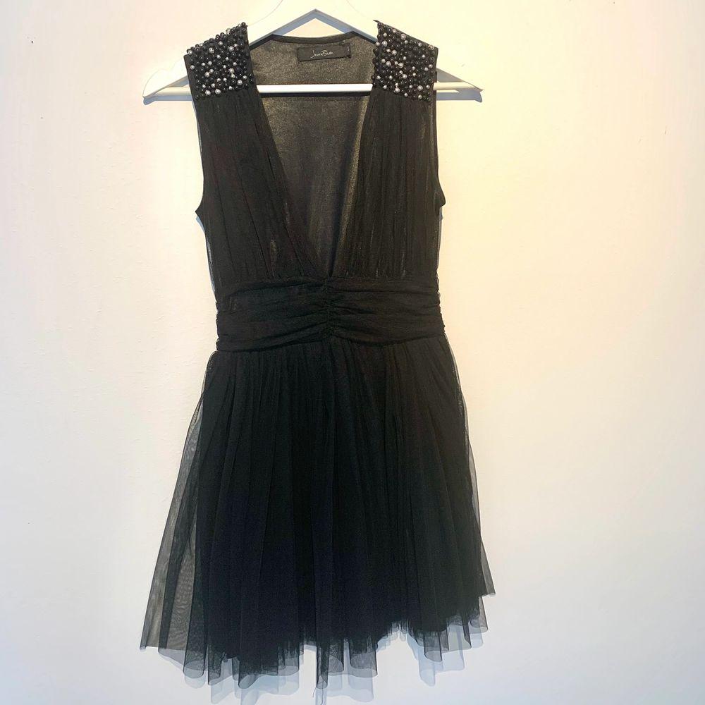 Helt ny festklänning från märket Jeane Blush, som tyvärr inte kommit till användning. Klänningens axlar pryds av vita och svarta pärlor. Klänningen stängs med en diskret dragkedja på sidan i midjan. Klänningen har en rätt djup v-ringning. Storlek S. . Klänningar.