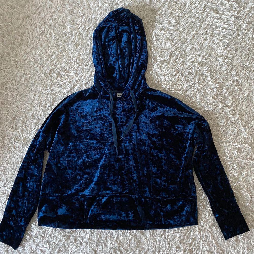 Lite croppad blå hoodie i materialet krossad sammet. Passar bra på mig som är 174 cm lång. Mycket bra skick, som ny. 💜FRAKT INGÅR I PRISET💜. Huvtröjor & Träningströjor.