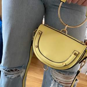 Gul handväska från Nelly. Helt oanvänd. Funkar som handväska eller med axelrem. Stängs med en magnet. Supercool verkligen men inte fått användning för den!💛 Kan skickas mot frakt!
