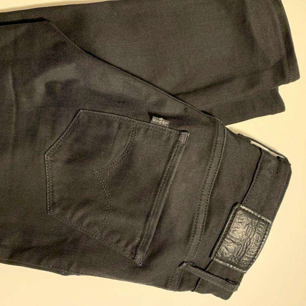Svarta, högmidjade Levis jeans i storlek 25. Nyskick utan slitningar eller bleknad färg.. Jeans & Byxor.