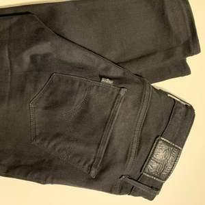 Svarta, högmidjade Levis jeans i storlek 25. Nyskick utan slitningar eller bleknad färg.