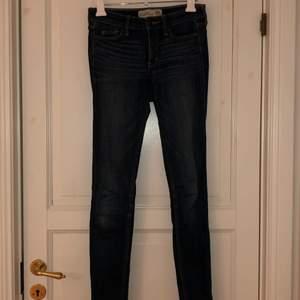 Skinny jeans i mörkblå tvätt, låga i midjan. En ljusare fläck på knät. Strl 00R W24 L31