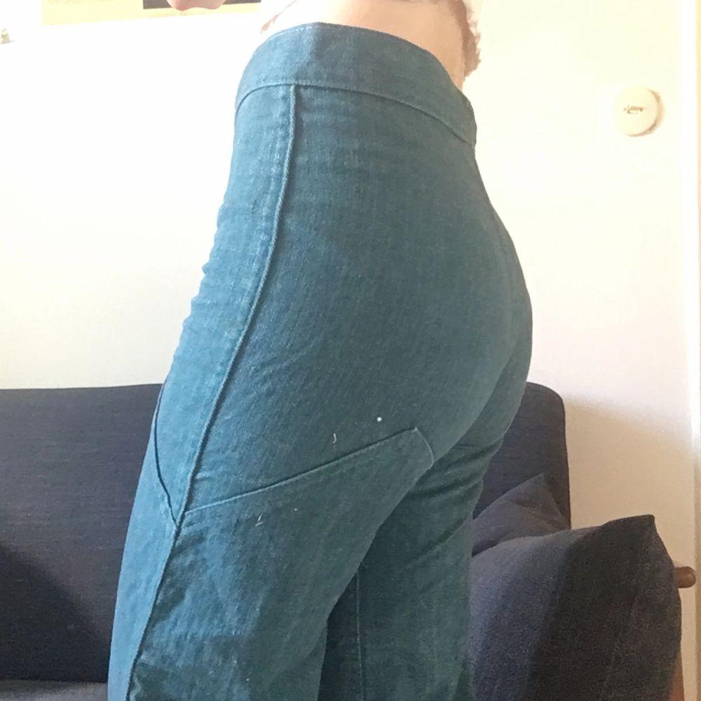Retrobyxor i 70talsstil. Mörkt grönblå/turkos färg. Köpta på Beyond Retro. Sitter tajt om rumpan, med vida, smått utsvängda ben. Passar strl 32. Priset kan sänkas vid snabb affär :). Jeans & Byxor.