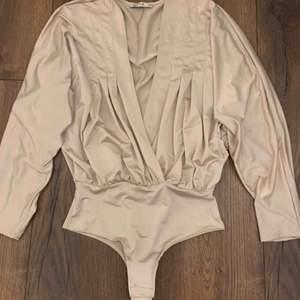 V-ringad body i silkes material från NELLY i storlek XS. Nästan helt oanvänd! På bilden ser den ut att vara mer beige, men skulle säga att den är mer i en rosa nyans i verkligheten. Frakt tillkommer ♥️