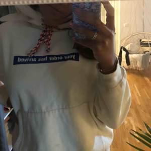 """Beige hoodie med trycket """"your order has arrived"""" fram till och trycker """"pick it up asap"""" på ena armen"""