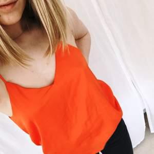 Topp med smala axelband från H&M. Färgen är stark orange vilket passar snyggt till slitna jeans!   Möts i Stockholm eller frakt 29kr