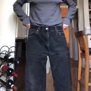 Svarta, äkta Levis-jeans som sitter jättefint på och är väldigt sköna. Lite balloon/boyfriend modell, men midjan är ganska liten i storleken. Den nedre delen av byxorna är upprullad.
