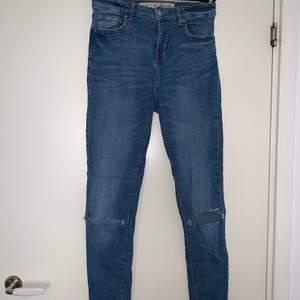 Blåa jeans med hål i knäna. Lågmidjade. Hämtas upp eller fraktas. Köparen står för frakt. Frakten ligger på ca 40kr. Skicka privat för bättre bild.