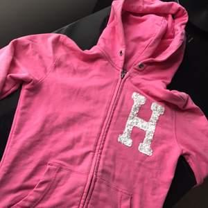 Tommy Hilfiger hoodie i strl. 164, vilket motsvarar XS.  Rosa med vita paljetter formade som ett H på bröstet.
