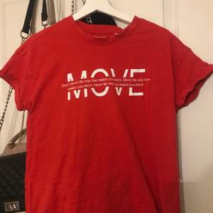 Röd T-shirt med ett tryck framtill. Det står MOVE stort och i den står det Dont move the way fear makes you move. Move the way love makes you move. Move the way joy makes you move. Använd fåtal gånger. Storlek S men skulle säga att den är mer som M i modellen.