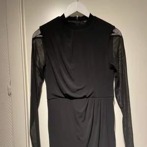 Klänning med mesh i ärmarna och lite olika sömnadsdetaljer. Dragkedja där bak och i bra skick. Frakt 50kr