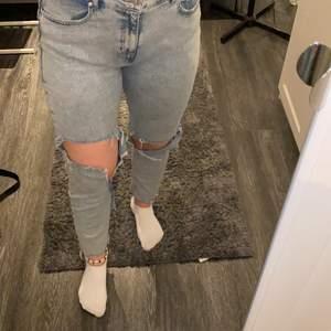 Blåa mom jeans med stora hål på knäna. Från reserved
