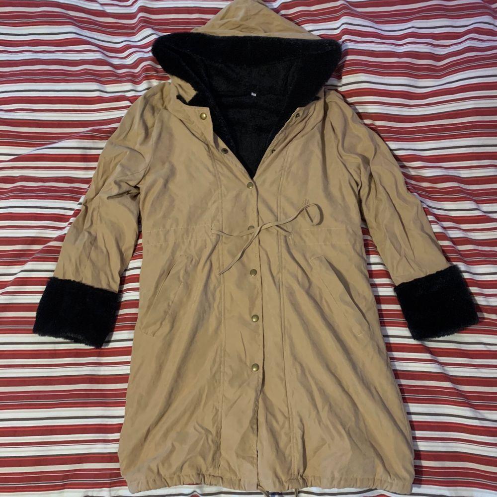 Lång beige mocka jacka med fluffigt svart fejk päls inne och med luva, jackan kommer över knäna. strl L, 100kr. Frakt tillkommer. . Jackor.