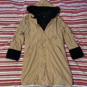 Lång beige mocka jacka med fluffigt svart fejk päls inne och med luva, jackan kommer över knäna. strl L, 100kr. Frakt tillkommer.