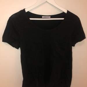 En enkel svart T-shirt från ZARA med en ficka ovanför vänster bröst