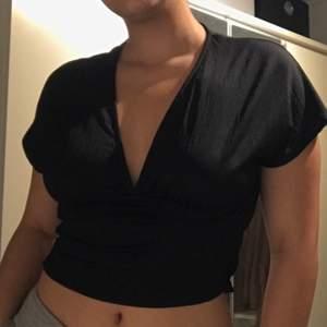 Svart V-ringad tröja med resår (skrynkligt)längst ner på baksidan. Oanvänd. Säljes pga ingen användning. Köparen står för frakt!
