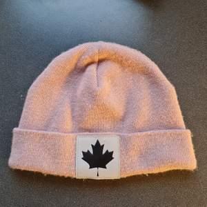 Ljusrosa mössa från Canada Snow, märket i fram är en reflex, använt ok skick.