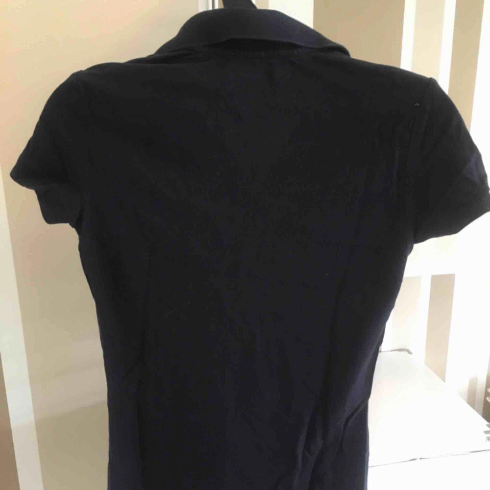 Marinblå piké från Tommy hillfiger. T-shirts.