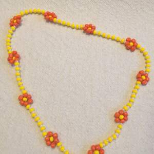 Fint gult och vitt halsband med orange blommor🍊 som jag gjort själv🧚🏼♀️. Om ni har några frågor är det bara att skriva🥰 Det är gjort med en elastisk tråd så det passar alla!