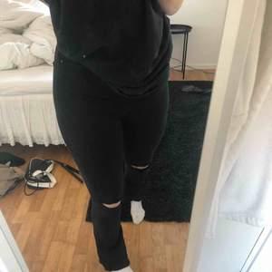 Svarta utsvängda jeans med slitningar nertill och hål på knäna. Fint skick!