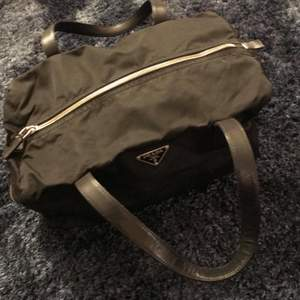 Mått: Höjd: cirka 18 cm Bredd: cirka 30 cm Djup: 16 cm Skick: 8.5/10, Säljer en väska tillverkad i nylontyg med silverfärgade metalldetaljer. Handtag i läder, väskan är märkt