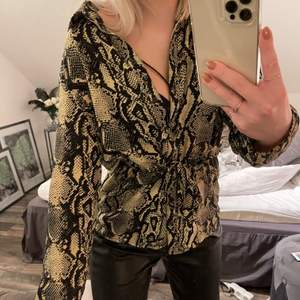 Säljer min fina skjort blus i ormskinnsmönster. Blusen är en storlek XS och har knytning runt midjan som man kan knyta hur man vill. Säljer för 80kr+frakt🦋💞💓