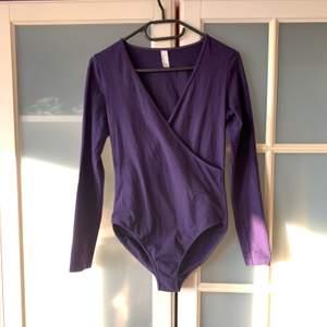 En lila Jersey American Apparel body, väldigt fin att ha under jeans och kjolar osv. Den är i bra skick!