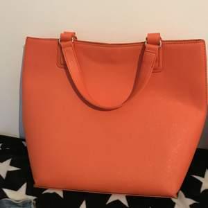 En jättefin orange handväska som är använd sparsamt