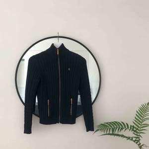 Kabelstickad marinblå Ralph Lauren tröja med gulddragkedja. Mycket bekväm och sparsamt använd. 🌞