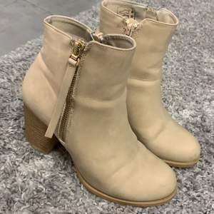 Beiga högklackade skor, med guld dragkedja på sidan och brun klack. Välanvända skor. Men i hyfsat fint skick