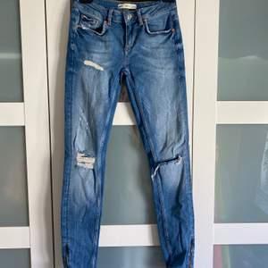 Säljer ett par jeans med hål i och även slits längst nere vid bena, i storlek 27/32