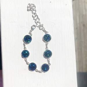 Superfint egentillverkat armband med blåa kluster som glittrar extremt fint i solen.