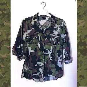 Kamouflagemönstrad skjorta från Newyorker i storlek L (funkar även i storlek M ifall du vill ha den något oversized). Går ner lite längre än höftbenet. Uppvikbara ärmar, 2 bröstfickor, och i material aningen strävare utanpå än bomullstyg.